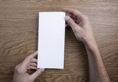 Mens hands holding white flyer royalty free stock photo
