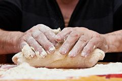 Mens hands knead dough. Mens hands knead the dough Royalty Free Stock Image