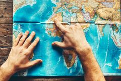 Mens Hands On A Paper Map Of The World Indicate The Final Destination, Top View Stock Images