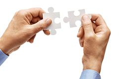 Mens hands in shirt holding one puzzle element and put together isolated on white background. Close up. High resolution product stock photo
