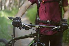 Mens in handschoenen met de fiets in het hout Stock Foto