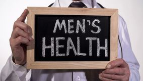 Mens health written on blackboard in urology doctor hands, reproductive medicine. Stock footage royalty free stock images
