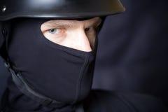 Mens in helm en masker dat bij u staart Stock Afbeelding