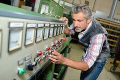 Mens het aanpassen controles op machine stock foto's