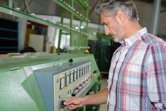 Mens het aanpassen controles op machine in fabriek royalty-vrije stock fotografie