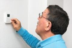 Mens het aanpassen thermostaat thuis, nadruk op thermostaat Celsius-temperatuurschaal stock foto's