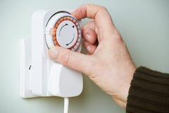 Mens het Aanpassen Tijdopnemer op Elektrocontactdoos stock afbeelding
