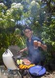 Mens het barbecuing in zijn tuin Royalty-vrije Stock Fotografie