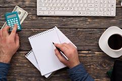 Mens het berekenen huisfinanciën bij een houten bureau Stock Afbeelding
