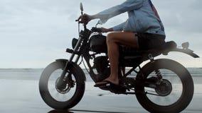Mens in het berijden van motorfiets op strand uitstekende motor op strandzonsondergang op Bali Jong hipstermannetje die van vrijh stock video