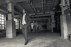 Mens het besteden tijd in donkere industriële zaal Stock Foto's
