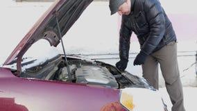 Mens het bevestigen auto met geopende kap stock videobeelden