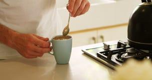 Mens het bewegen koffie in keuken thuis 4k stock footage
