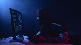 Mens het binnendringen in een beveiligd computersysteem computerzitting in een donkere ruimte Zwarte rookachtergrond stock videobeelden