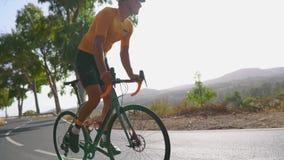 Mens het cirkelen op de openluchtoefening van de wegfiets op een lege weg in de ochtend Extreem Sportconcept Langzame Motie