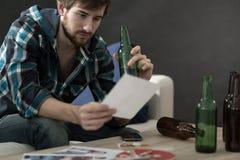 Mens het drinken alcohol en het bekijken foto's Royalty-vrije Stock Afbeelding