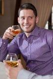 Mens het drinken cognac met vriend stock foto's
