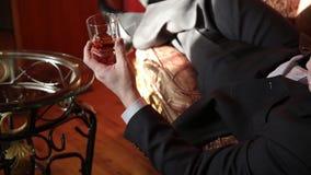 Mens het drinken de brandewijn, zet het glas op de koffietafel en irritably het uitnodigen van de telefoon stock video