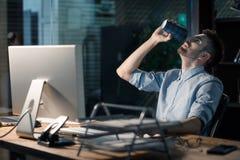 Mens het drinken koffie die overhours werken royalty-vrije stock fotografie