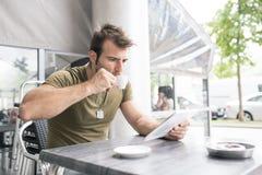 Mens het drinken koffie en laptop tabletcomputer in het terras stock fotografie