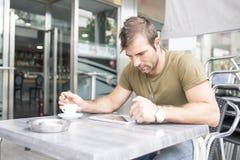 Mens het drinken koffie en laptop tabletcomputer in het terras aangaande stock afbeelding