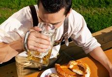 Mens in het drinken Lederhosen bier royalty-vrije stock afbeelding