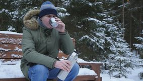 Mens het drinken thee in de winterbos stock video