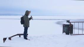 Mens het drinken thee van thermosflessen op achtergrond van bevroren rivier stock videobeelden