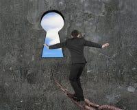 Mens het in evenwicht brengen op oude ijzerketting naar sleutelgat met hemel Stock Foto