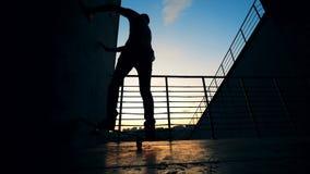 Mens het in evenwicht brengen op twee wielen op een skateboard, langzame motie stock videobeelden