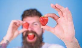 Mens het gebaarde defocused knipogen met rode bes, Lange baard van mensen eet de knappe hipster greepaardbei Bekijk mijn bes stock foto's
