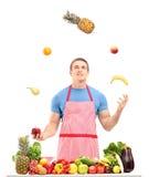 Mens het jongleren met met vruchten achter een lijsthoogtepunt van vruchten en veget Royalty-vrije Stock Foto's