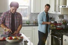 Mens het koken draait aan vriend, die ingrediënten hakt stock afbeelding