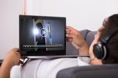 Mens het letten op film op laptop stock fotografie