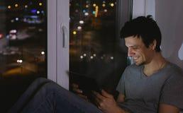 Mens het letten op video op telefoon en het lachen Het zitten op de vensterbank in de donkere nacht Stock Fotografie