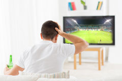 Mens het letten op voetbal en het drinken bier thuis Royalty-vrije Stock Foto