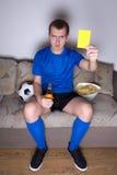 Mens het letten op voetbal op TV en het tonen van gele auto Royalty-vrije Stock Afbeeldingen