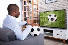 Mens het Letten op Voetbalwedstrijd op Televisie stock foto's