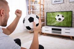 Mens het Letten op Voetbalwedstrijd op Televisie stock afbeeldingen