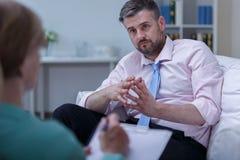 Mens het luisteren therapeutraad Stock Fotografie