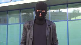 Mens in het masker die zich openlucht bevinden De rover, intimideert, gangster, misdadiger, schurk stock video