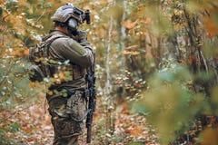 Mens in het militaire eenvormige spreken op zijn mobiele telefoon stock afbeelding