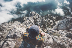 Mens het ontspannen alleen op rotsachtige bergenklip over wolken Stock Afbeeldingen