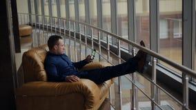 Mens het ontspannen als zijn voorzitter en het genieten van de van mening van bureauvenster stock videobeelden
