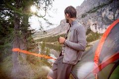 Mens het ontspannen dichtbij het hangen van tent die met hete drank kamperen die meerpanorama bekijken Groep de zomer van vriende Stock Foto