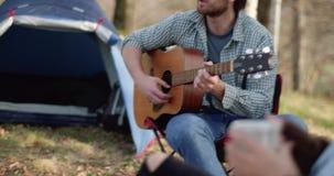 Mens het ontspannen door gitaar rond brandplaats met hete drank dicht te spelen echte vriendenmensen openlucht het kamperen tent stock footage