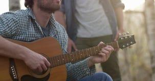 Mens het ontspannen door gitaar rond brandplaats met hete drank dicht te spelen echte vriendenmensen openlucht het kamperen tent stock videobeelden