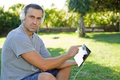 Mens het ontspannen met tabletpc Stock Foto
