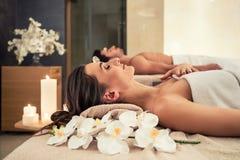 Mens het ontspannen met zijn partner op massagebedden op wellnesscentrum royalty-vrije stock afbeeldingen