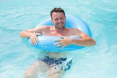 Mens het ontspannen op de luchtboei in het zwembad concept over vakantie en vrije tijd royalty-vrije stock afbeeldingen